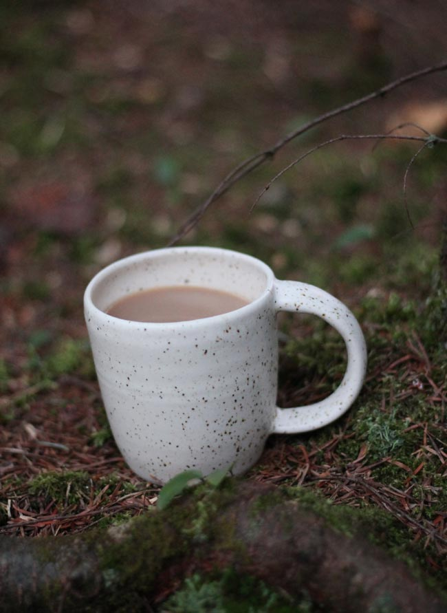 white-speckled-mug-in-moss
